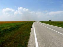 Estrada asfaltada nos campos Foto de Stock Royalty Free