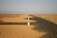 Estrada asfaltada preta completamente da areia Foto de Stock