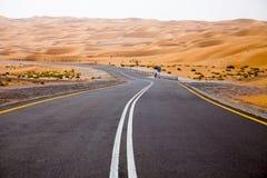 Estrada asfaltada preta de enrolamento através das dunas de areia de oásis de Liwa, Emiratos Árabes Unidos Imagens de Stock Royalty Free