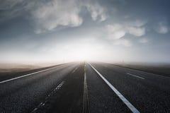 Estrada asfaltada que sae em uma luz brilhante Imagem de Stock Royalty Free