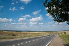 Estrada asfaltada que vai ao horizonte em um dia de ver?o ensolarado imagens de stock
