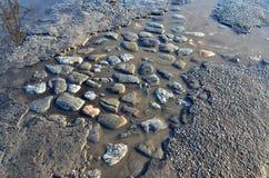Estrada asfaltada quebrada com furos e poças na mola adiantada Fotografia de Stock Royalty Free