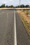 Estrada através das colheitas secadas Foto de Stock Royalty Free