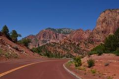 Estrada através das rochas vermelhas Fotografia de Stock Royalty Free