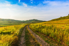 A estrada através do campo entre montes Foto de Stock
