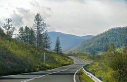 Estrada através do terreno montanhoso com árvores e nuvens no céu azul fotos de stock