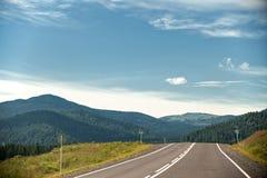Estrada através do terreno montanhoso com árvores e nuvens no céu azul imagem de stock