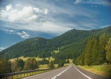Estrada através do terreno montanhoso com árvores e nuvens no céu azul imagens de stock