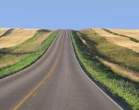 Estrada através dos campos de trigo da pradaria fotografia de stock