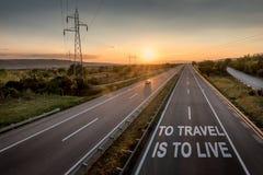 A estrada bonita com um único carro no por do sol com a mensagem inspirador a viajar é viver foto de stock royalty free