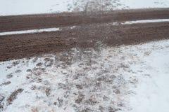 Estrada coberto de neve no inverno, traços das estradas transversaas de pedestres e carros na estrada suja Fotografia de Stock