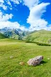 A estrada com pneu segue a condução às montanhas Fotos de Stock Royalty Free