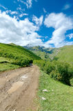 A estrada com pneu segue a condução às montanhas e Fotografia de Stock