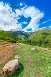 A estrada com pneu segue a condução às montanhas e Fotos de Stock Royalty Free
