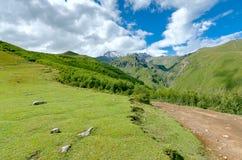A estrada com pneu segue a condução às montanhas e Foto de Stock Royalty Free