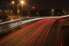 Estrada com tráfego de carro na noite com luzes obscuras Imagens de Stock Royalty Free