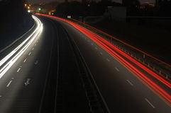 Estrada com tráfego de carro na noite com luzes obscuras Fotografia de Stock
