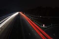 Estrada com tráfego de carro na noite com luzes obscuras Imagem de Stock