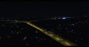 Estrada com tráfego de fluxo com uma área urbana na opinião aérea da noite vídeos de arquivo