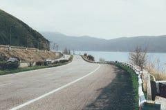 Estrada com um fundo do lago e das montanhas fotos de stock royalty free