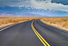 Estrada curvada com montanhas Fotos de Stock Royalty Free