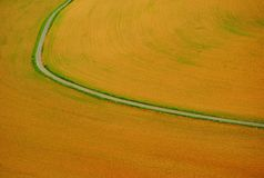 A estrada curvada corta o campo em duas metades imagens de stock royalty free