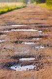 Estrada da argila vermelha com furos Imagens de Stock Royalty Free