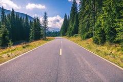 Estrada da montanha Ajardine com rochas, o céu ensolarado com nuvens e o b Imagem de Stock Royalty Free