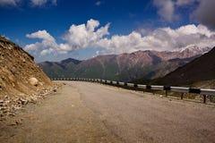 A estrada da montanha com volta e uma proteção oposta ao pico alto Fotografia de Stock Royalty Free
