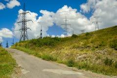 Estrada da montanha perto da linha elétrica de alta tensão fotografia de stock royalty free