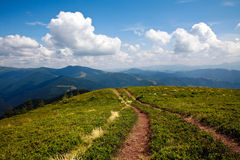 Estrada da montanha que conduz ao horizonte sob um céu azul Imagens de Stock
