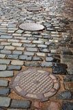 Estrada da pedra com os portais do esgoto do ferro fundido Imagem de Stock Royalty Free