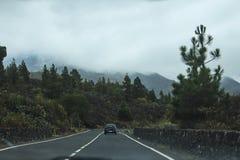 Estrada da serpentina com montanhas cobertas na opinião da névoa foto de stock