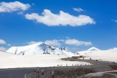Estrada da serpentina da montanha entre montanhas na neve, fundo do céu azul imagem de stock