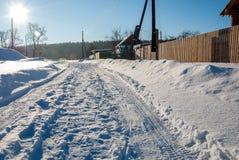 A estrada da vila do inverno com uma trilha do carro Fotografia de Stock Royalty Free