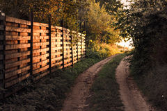 Estrada da vila perto da cerca de madeira no por do sol Imagem de Stock