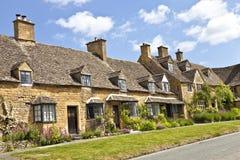 A estrada de casas de campo encantadores da vila com verão jardina Imagem de Stock Royalty Free
