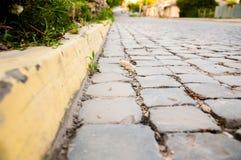 Estrada de cidade alinhada com blocos de pedra Beiras amarelas ?rvore no campo foto de stock royalty free
