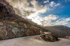Estrada de enrolamento com os penhascos vulcânicos coloridos à porta de Athinios, Santorini fotos de stock royalty free