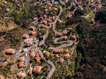 Estrada de enrolamento da montanha às curvaturas, às casas com o telhado vermelho telhado, à piscina e à garagem Vista superior a fotografia de stock