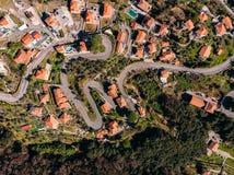 Estrada de enrolamento da montanha às curvaturas, às casas com o telhado vermelho telhado, à piscina e à garagem Vista superior a fotografia de stock royalty free