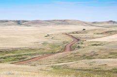 Estrada de enrolamento do campo em um estepe montanhoso imagem de stock