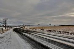 Estrada de enrolamento em um campo de neve imagens de stock