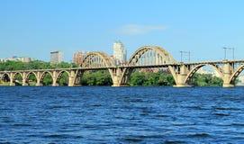 A estrada de ferro arqueou a ponte através do rio de Dnieper com uma vista da cidade de Dnipro Imagem de Stock Royalty Free