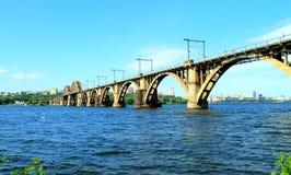 A estrada de ferro arqueou a ponte através do rio de Dnieper com uma vista da cidade de Dnipro Fotos de Stock Royalty Free