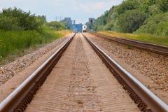 Estrada de ferro com o trem na distância Imagens de Stock Royalty Free