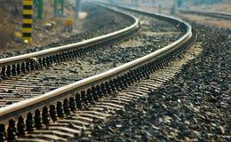 Estrada de ferro de dobra com centenas de seixos, ao lado dela foto de stock