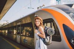 Estrada de ferro e curso do tema Mulher caucasiano nova do retrato com o sorriso toothy que está no fundo do trem do estação de c foto de stock royalty free