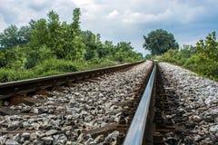 Estrada de ferro longa contra o céu nebuloso azul bonito na natureza foto de stock royalty free