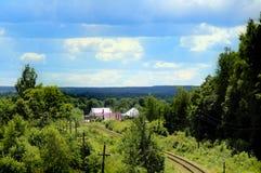 Estrada de ferro que passa através da floresta e perto da vila imagens de stock royalty free